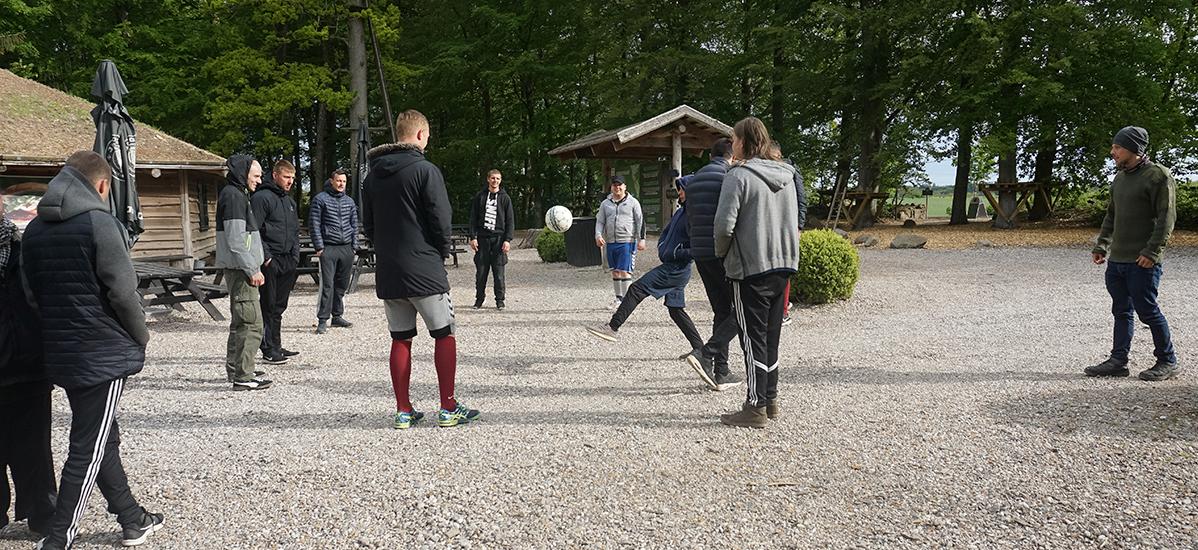 Traineerne spiller bold i ude i grus gården