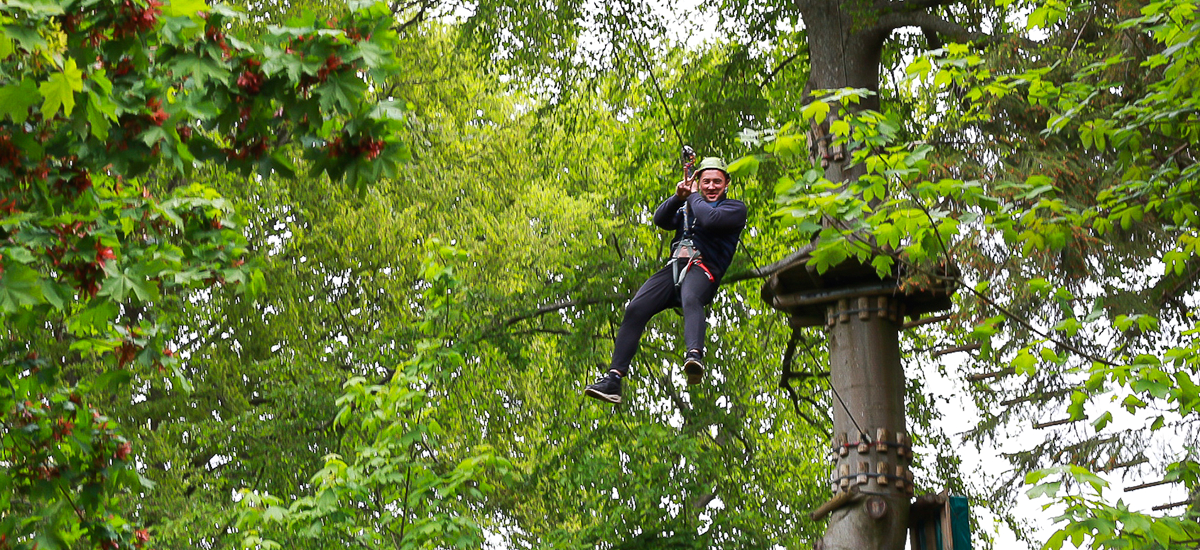 En Tagdækker Trainee oppe i tagtoppene, som er i gang med ziplining
